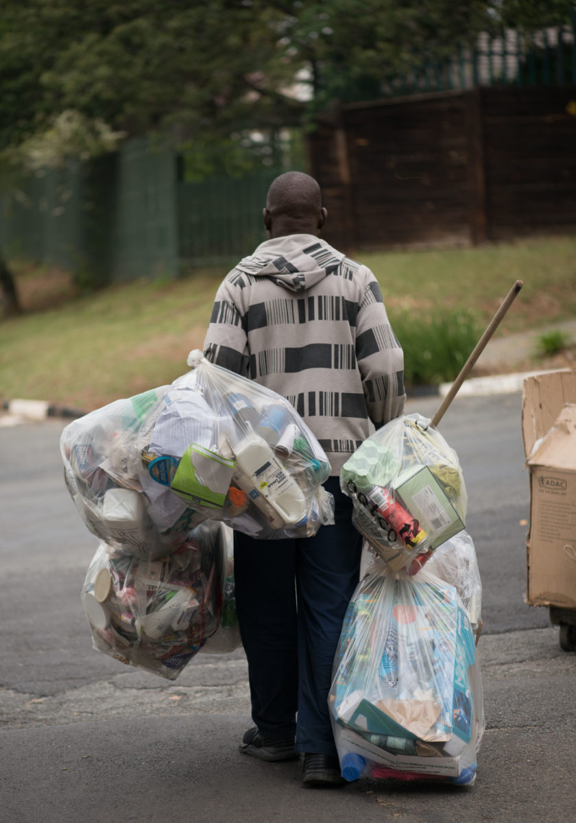 Waste reclaimer walking down the road with bags of plastic waste.