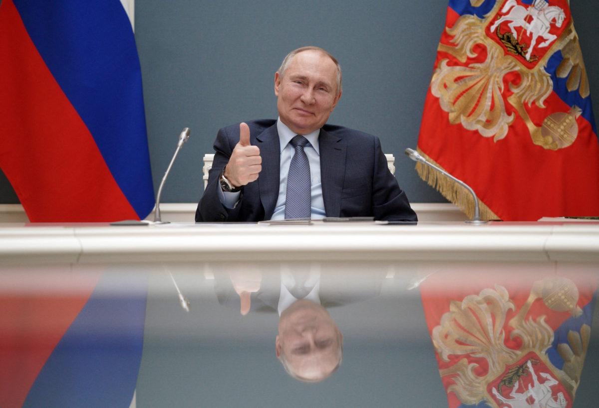 Putin sitting behind a table