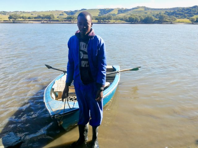 Boat operator Ntobeko Ntlanganiso ferries people across the Xhora River to get to the clinic. Photo: Johnnie Isaac / Groundup
