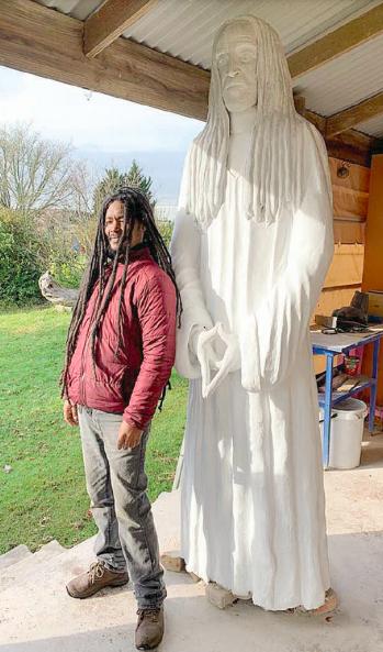 Eugene Lewis and his statue of a Rastafari priest.