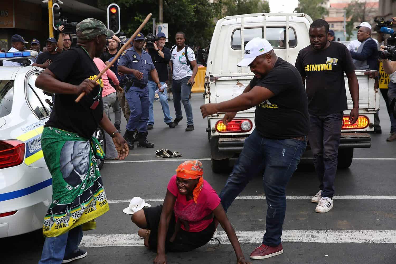 ANC branch secretary in Inner City Zone 12 Thabang Setona kicks a female Black Land First (BLF) member outside Luthuli House on 5 February 2018 in Johannesburg